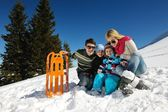 Family having fun on fresh snow at winter vacation — Stock Photo