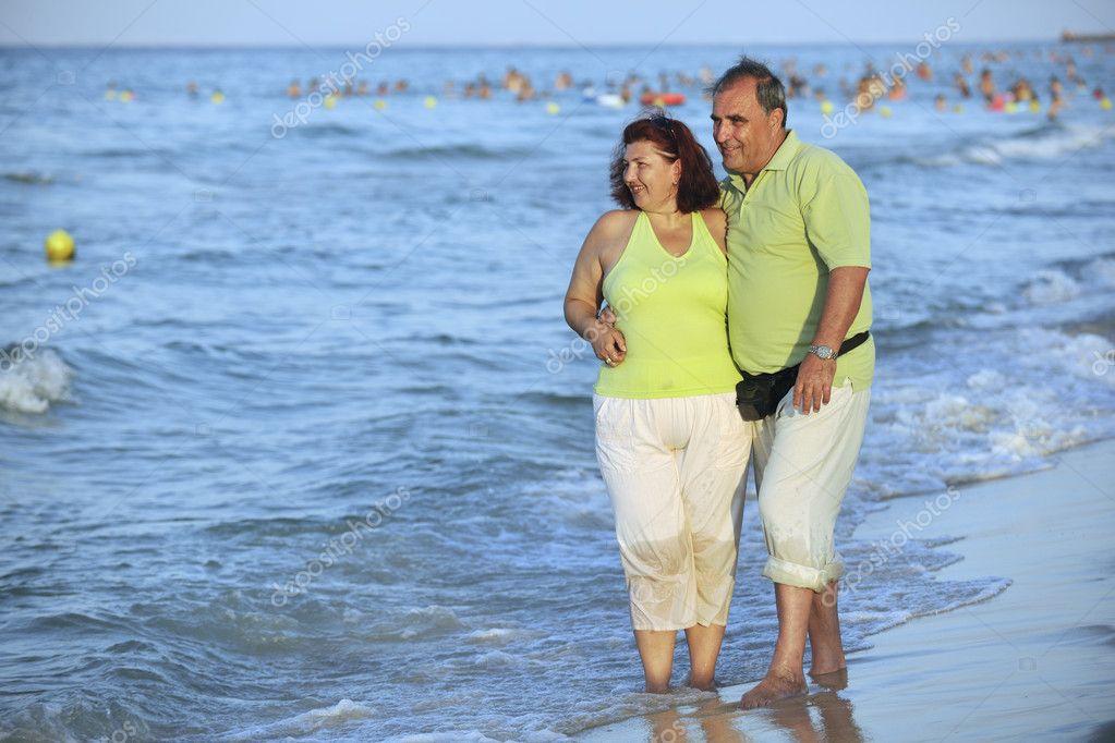 快乐高级成熟老年夫妇在日落海滩上有浪漫时间