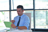 Affärsman med tablett compuer på kontor — Stockfoto