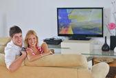 расслабленной молодая пара, смотреть телевизор у себя дома — Стоковое фото