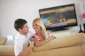 Relaxed young couple watching tv at home — Stock Photo