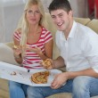 Couple at home eating pizza — Stok fotoğraf
