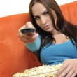 Постер, плакат: Woman eat popcorn and watching tv