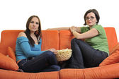 Female friends eating popcorn and watching tv — Stock Photo