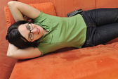 Happy young woman relax on orange sofa — Stock Photo