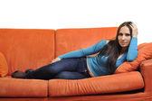 Vrouw ontspannen op oranje sofa — Stockfoto