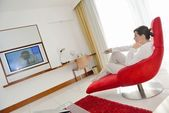 Young woman watching tv at home — Stock Photo