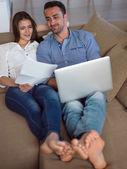 Détendue jeune couple travaillant sur ordinateur portable à la maison — Photo