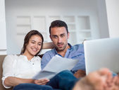 Relaxed young couple working on laptop computer at home — Stock Photo