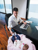 Man working from home and take care of baby — Stock Photo