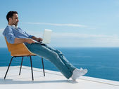 Relaxed young man at home on balcony — Stock Photo
