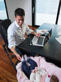 Man working from home and take care of baby — Stok fotoğraf