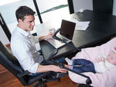 Man working from home and take care of baby — Stockfoto