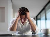 Frustrado hombre de negocios joven que trabaja en la computadora portátil en casa — Foto de Stock