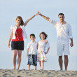 Family on beach showing home sign — Stock Photo #5780582