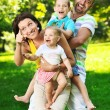 Happy young couple with their children have fun at park — Stock Photo #6821029