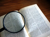Book and magnifying glass — Stock Photo