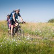 Father with daughter cycling - Stock Photo