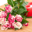 Beautiful roses and red candle in the shape of a heart. — Stockfoto