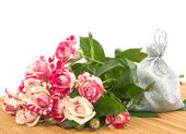 Bouquet of roses and a gift to the substrate. — Stock Photo