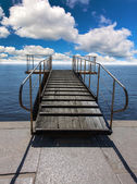 Pier in sea under blue sky and clouds — Stock Photo