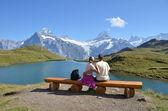 Travelers on a bench enjoying Alpine panorama. Jungfrau region, — Stock Photo