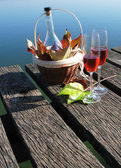 Two wineglasses and autumn leaves on a wooden jetty — Stock Photo
