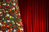 Christmas tree against red drapery — Stock Photo