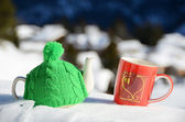 Tea pot in the knitted cap and red cup with a heart in the snow — Stock Photo