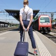 Stock Photo: Girl with a suitcase at the train station