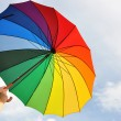 Rainbow umbrella in the hands — Stock Photo