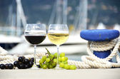 Wineglasses and grapes on the pier — Stock Photo