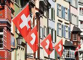 Old street in Zurich decorated with flags for the Swiss National — Stock Photo