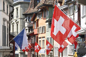 Old street in Zurich decorated with flags for the Swiss National — Foto Stock