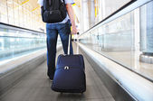 Traveler with a suitcase on the speedwalk — Stockfoto