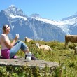 Girl with a jug of milk and a cow. Jungfrau region, Switzerland — Stock Photo