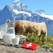 Swiss chocolate and jug of milk against mountain peak. Switzerla — Stock Photo