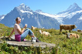 Girl with a jug of milk and a cow. Jungfrau region, Switzerland — Foto Stock