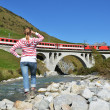 Girl looking at the train, which crosses a bridge. Switzerland — Stock Photo