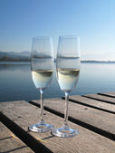 Two champagne glasses against a lake — Stock Photo