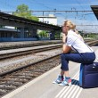 Girl at the railway station waiting for a train — Stock Photo