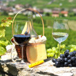 Stock Photo: Two wineglasses, grapes and cheese against vineyards. Switzerlan