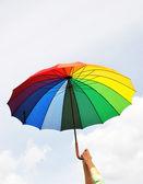 Rainbow umbrella in the hands — Stock Photo