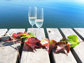 Two winglasses and autumn leaves on a wooden jetty — Stock Photo