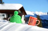 Teiera in maglia cappello e coppa rossa con un cuore sulla neve — Foto Stock