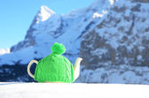 Tea pot in the knitted cap on the snow against mountain peak — Stock Photo