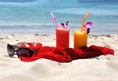 Pair of fruit shakes, red shawl and sunglasses on the tropical b — Stock Photo
