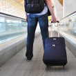 Traveller with suitcase on speedwalk — Stock Photo #21027487