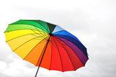 Paraguas arco iris contra el cielo nublado — Foto de Stock