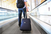 Cestovatel s kufrem na speedwalk — Stock fotografie
